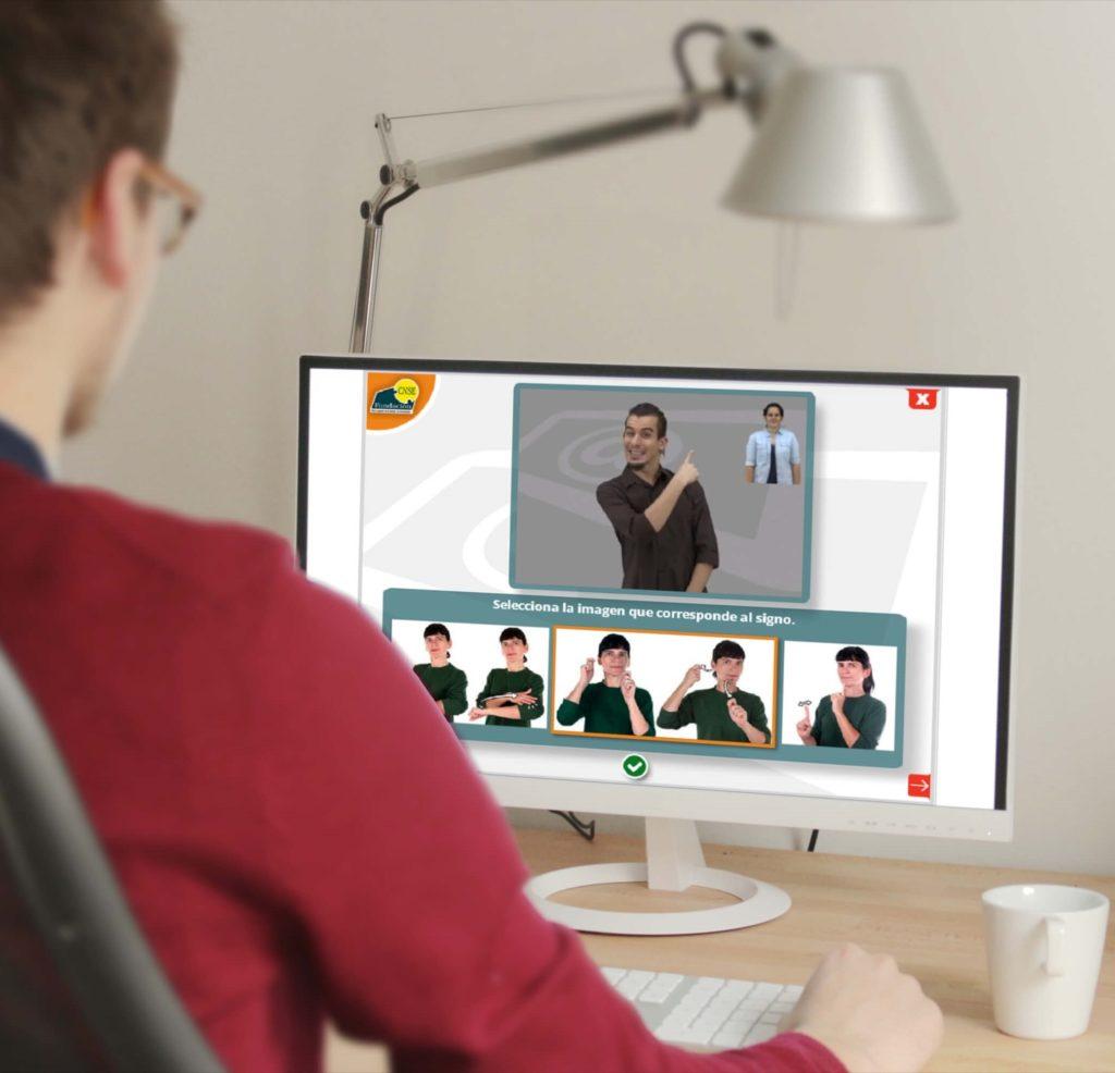 Chico de espaldas, jersey rojo y gafas, mira una pantalla de ordenador con imágenes de clases de lengua de signos, hay una taza blanca en la mesa