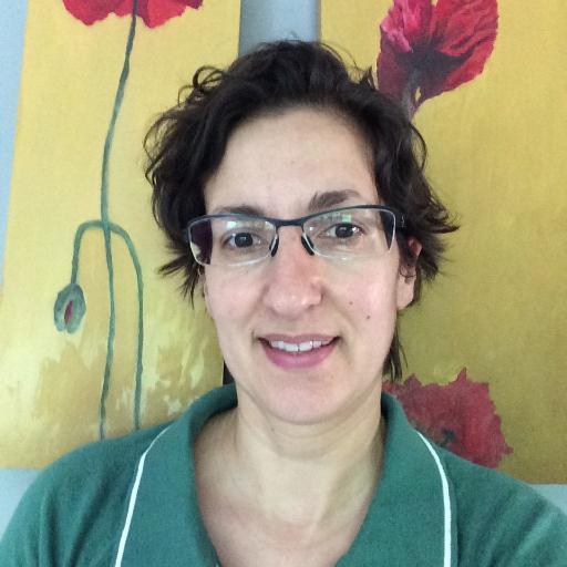 Arancha Díez tiene pelo corto, gafas y camisa verde, al fondo se ve un estampado de pared color amarillo y flores rojas