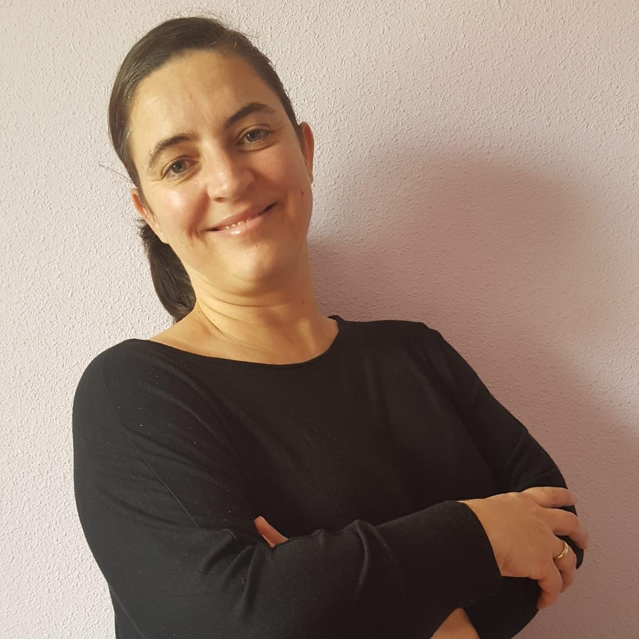 Carmen Blanco tiene pelo moreno largo recogido en una coleta y una camiseta negra de manga larga