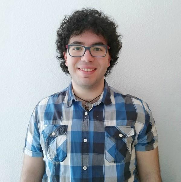 Julio tiene pelo rizado moreno y corto, gafas, camisa de cuadros azules y blancos, lleva un colgante con un adorno redondo
