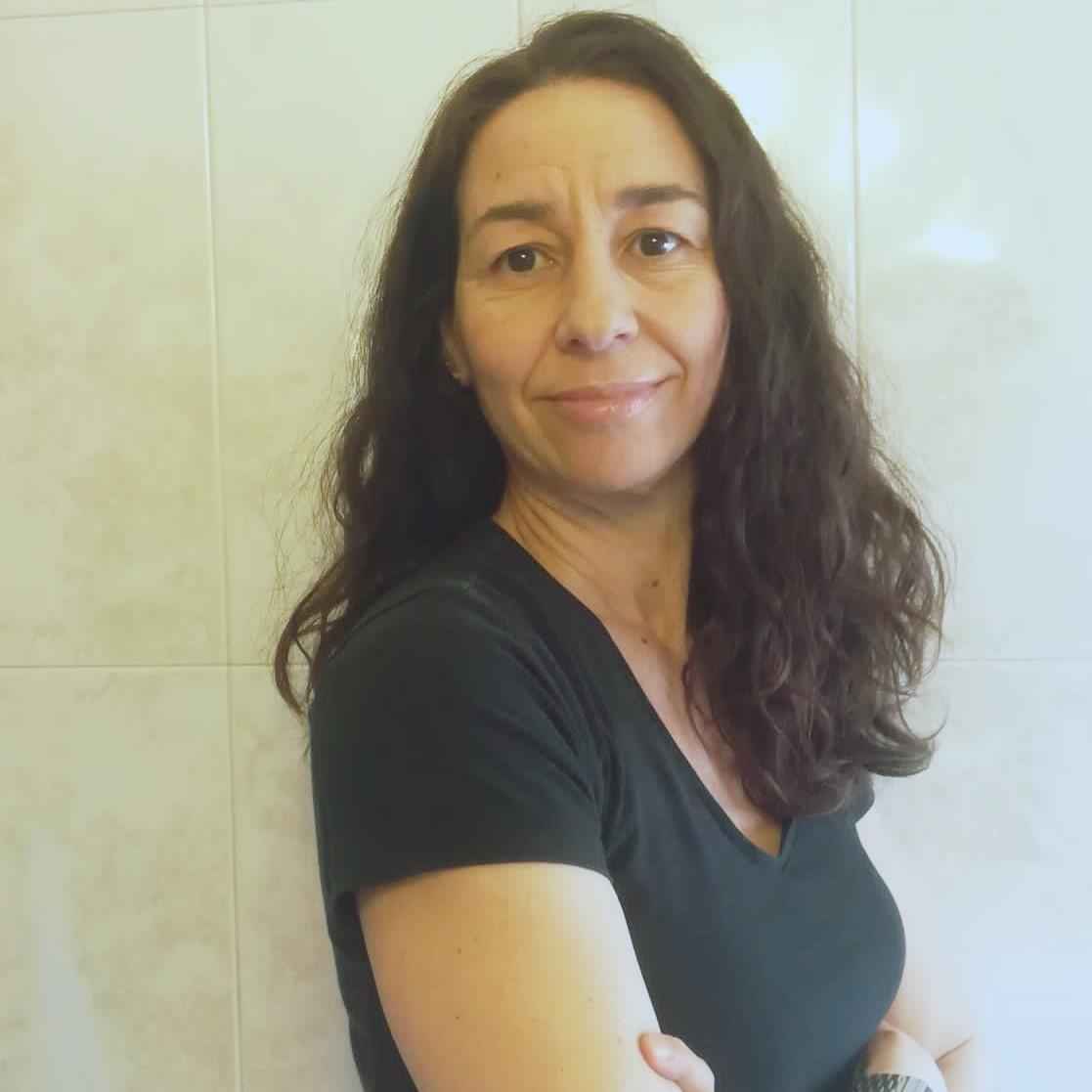 María Ángeles Abadía tiene pelo largo ondulado y castaño, ojos castaños y camiseta negra con cuello de pico