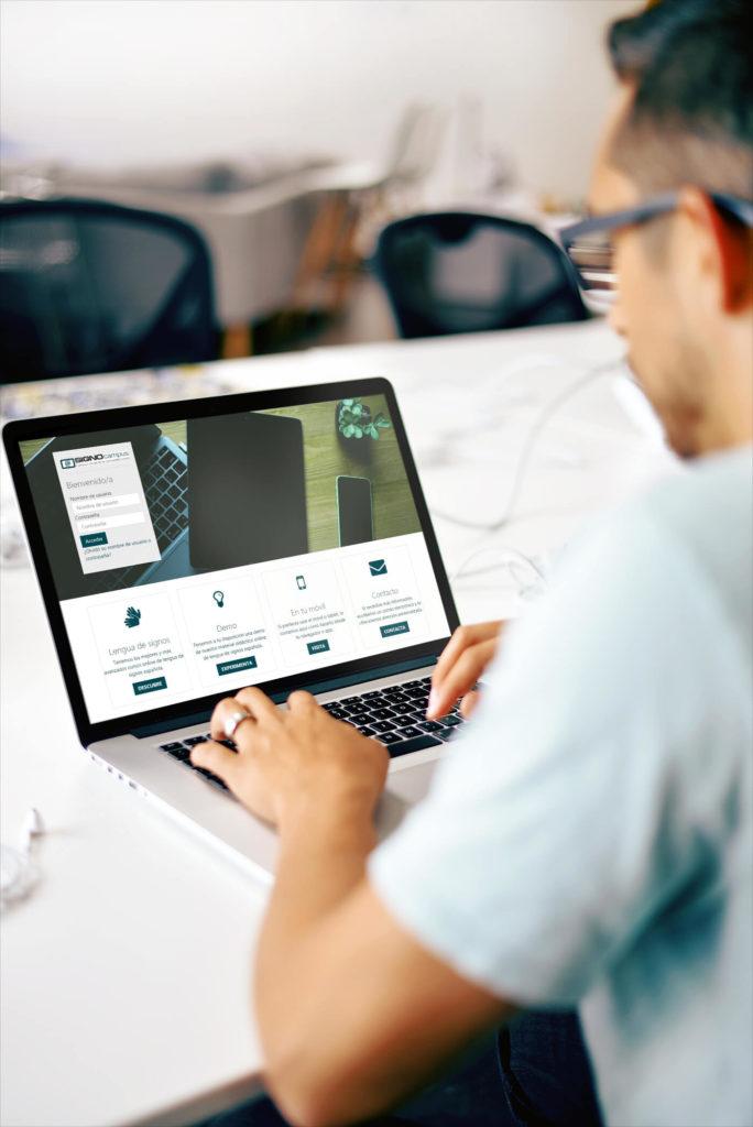 Una persona de espaldas, gafas y camiseta teclea en el ordenador portátil de la mesa, en la pantalla hay un acceso a la plataforma signocampus