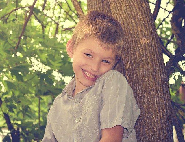 Niño de aproximadamente diez a doce años, pelo rubio y corto, sonrisa amplia, camisa color gris y rayas verticales blancas, apoyado en un árbol