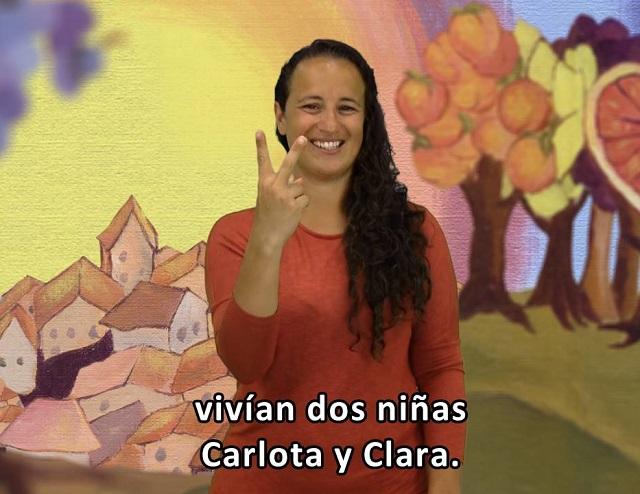 """Mujer de pelo largo ondulado, camiseta roja de manga larga, hace el signo del número dos. El subtítulo dice """"vivían dos niñas Carlota y Clara"""". Al fondo un paise de un pueblo y árboles frutales"""