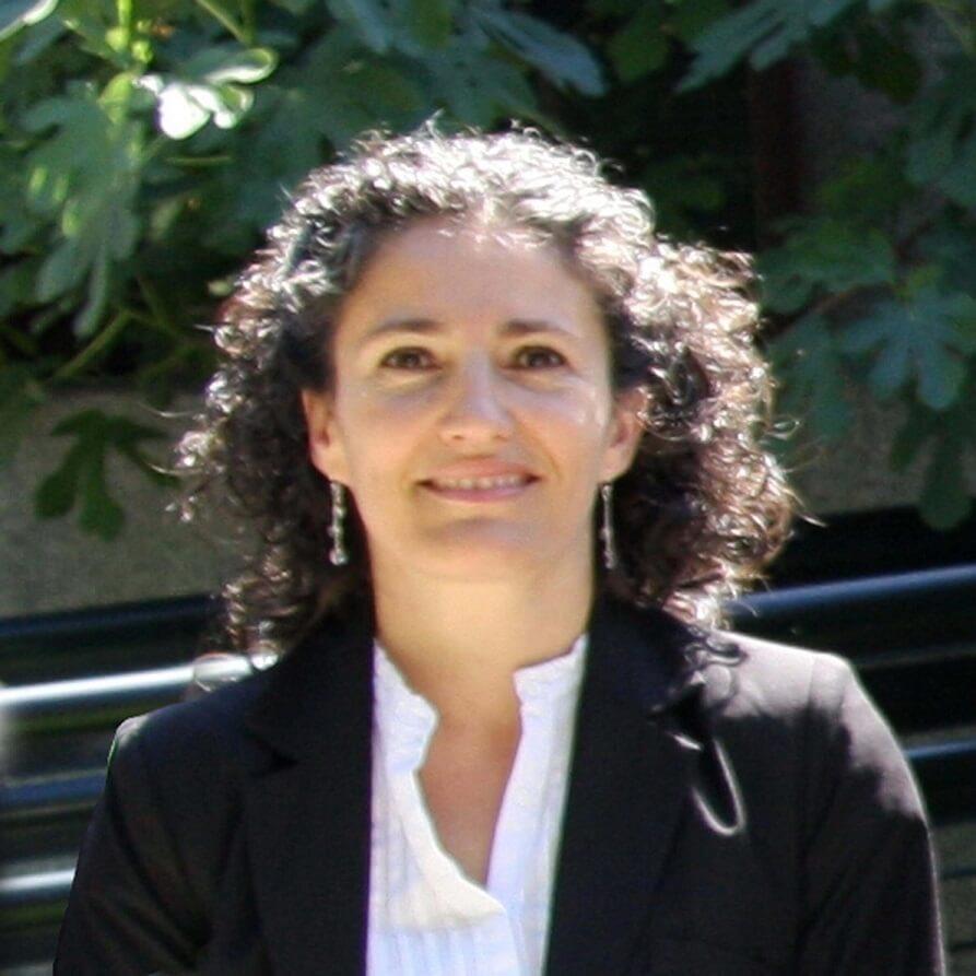 Mariluz tiene pelo ondulado, ojos marrones, chaqueta negra y blusa blanca